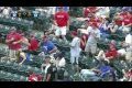 Fan grabs a foul ball without having to interrupt his cell conversation